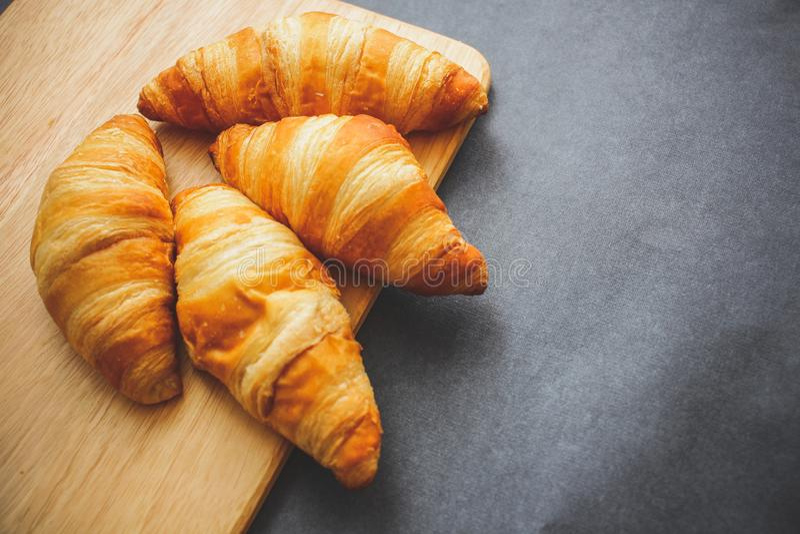 Cztery croissants na drewnianej lekkiej tnącej desce na ciemnym rzemiośle tapetują obrazy royalty free