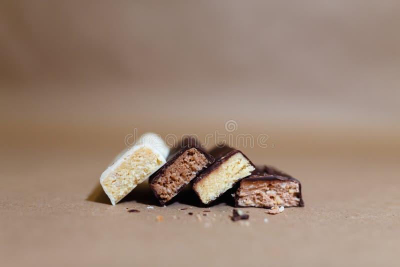 Cztery czekolada proteinowego baru z różnymi smakami w kontekście kropią ryżowych płatki na pieczenie papierze, Teflon papier Ser zdjęcie royalty free