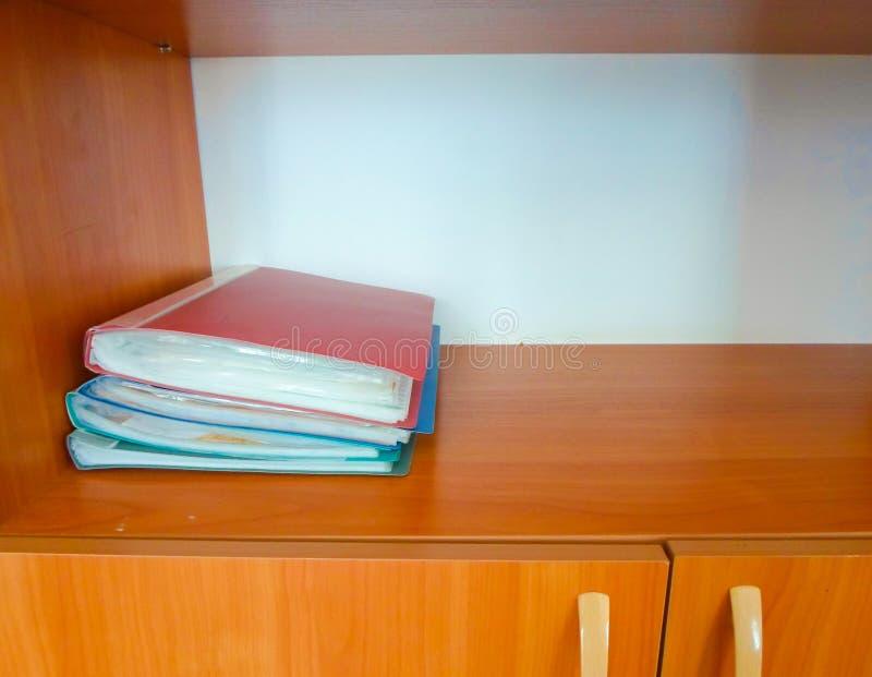 Cztery czerwone i niebieskie foldery na drewnianej półce w szafie fotografia royalty free