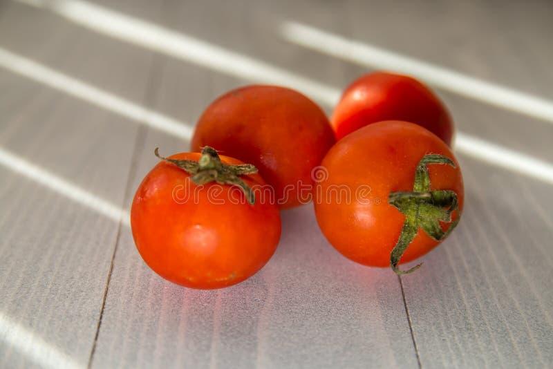 Cztery czerwonego organicznie pomidoru na białym drewnianym stole zdjęcia stock