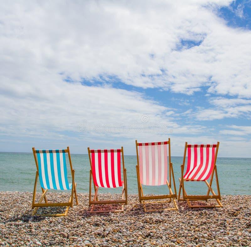 Cztery Deckchairs Na otoczak plaży obraz stock