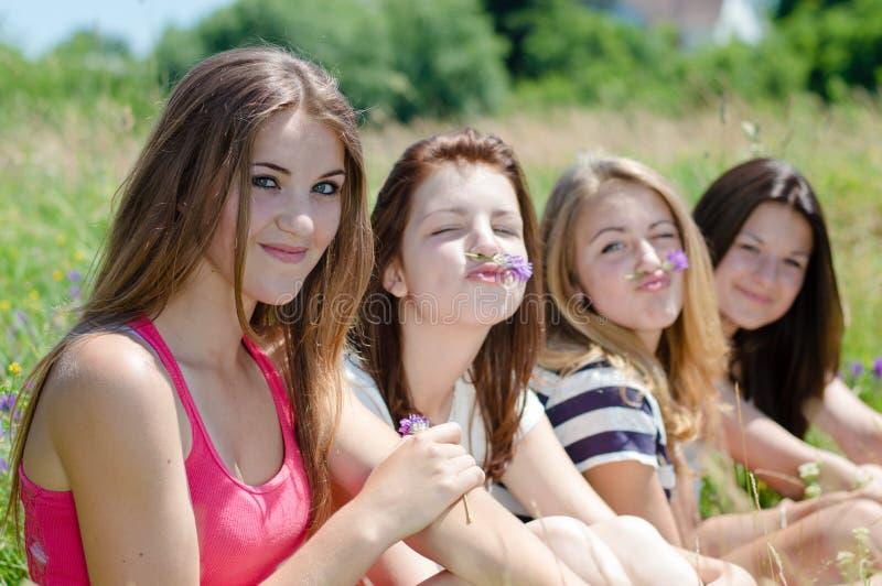 Cztery dosyć szczęśliwej uśmiechniętej młodej kobiety siedzi wpólnie na zielonym gazonie obraz royalty free