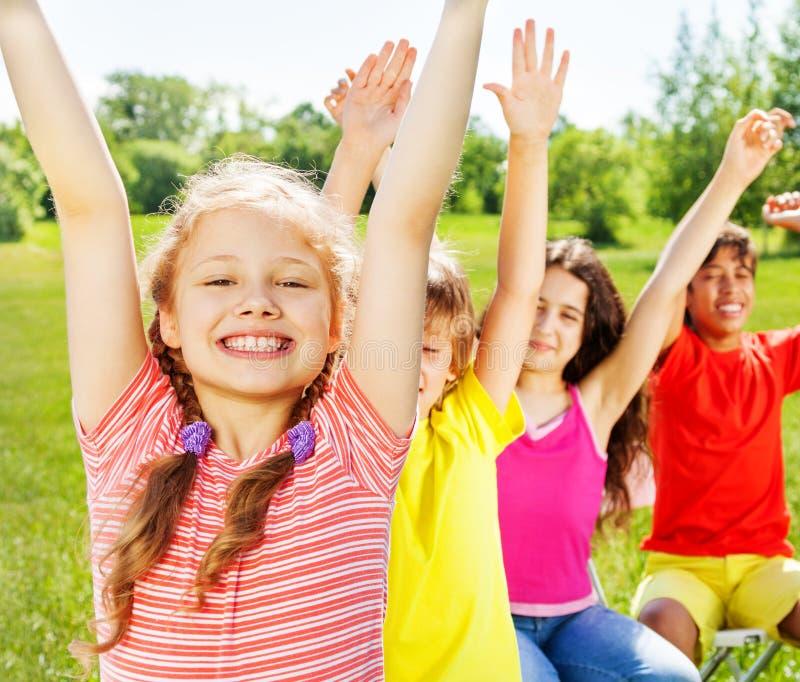 Cztery dziecka siedzi w rzędzie z rękami up obrazy royalty free