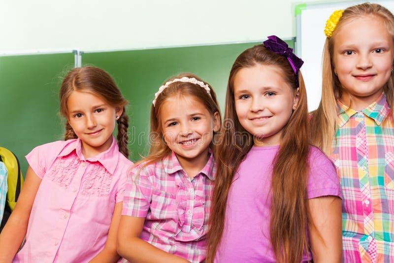 Cztery dziewczyn piękny stojak zamknięty w sala lekcyjnej fotografia stock