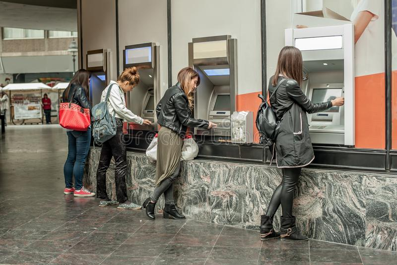 Cztery dziewczyna przyjaciela wycofuje pieniądze od kredytowej karty przy ATM zdjęcia stock