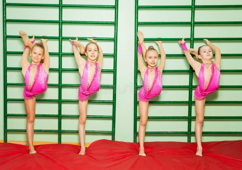 Cztery dziewczyny rozciąga nogi podczas gimnastycznej klasy zdjęcia stock