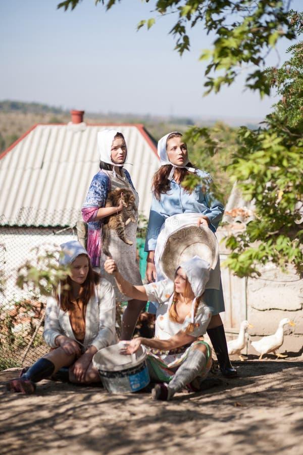 Cztery kobiety są ruchliwie działaniem w jardzie Retro styl, wieś, gospodarstwo rolne fotografia stock