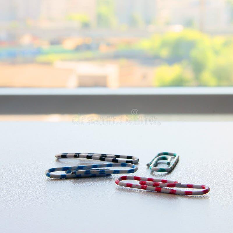Cztery koloru lampasa plastikowego paperclips na białym biurze zgłaszają zbliżenie zdjęcia stock