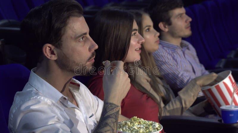 Cztery kumpel siedzi przy premiera film przy kinem fotografia royalty free