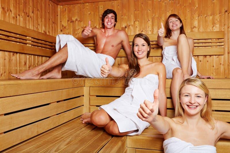 Cztery ludzie w sauna mienia kciukach obrazy stock