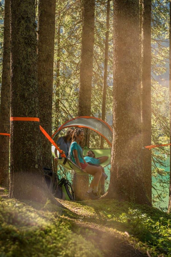 Cztery mężczyzna i kobiety szczęśliwy wiszący namiotowy camping w lasowych drewnach podczas słonecznego dnia blisko jeziora Grupa zdjęcie stock
