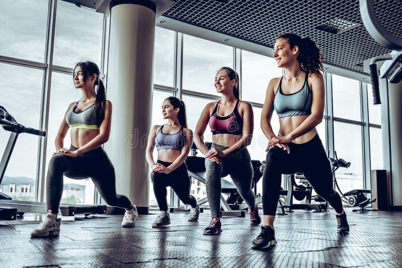 Cztery młoda sporty dziewczyna z sportowym ciałem robi opadom w gym zdjęcia stock