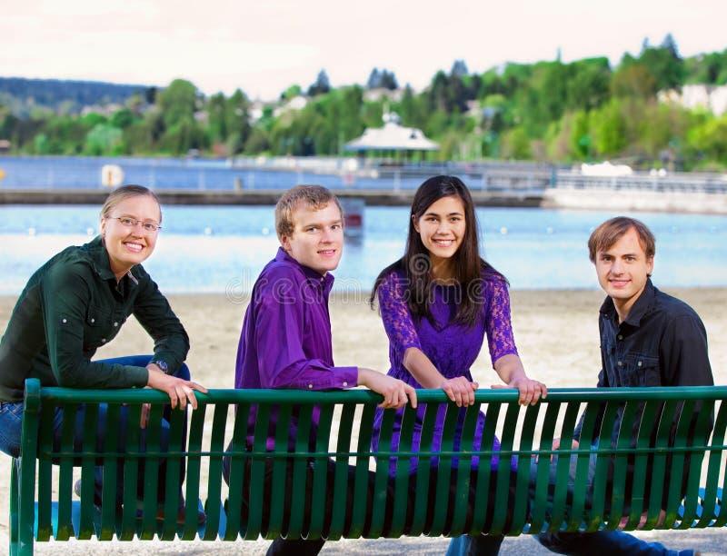 Cztery młodego wielo- etnicznego przyjaciela wpólnie przy plażą fotografia royalty free