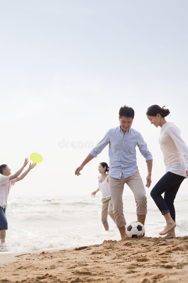 Cztery młodzi ludzie bawić się piłkę nożną i Frisbee na plaży, Chiny fotografia stock