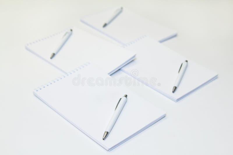 Cztery notepads z piórami na białym tle pusta kopii przestrzeń Mockup obrazy royalty free
