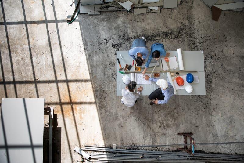 Cztery persons drużyna inżyniery opowiada wpólnie przeglądać materiał budowlanego i brainstorm o szczegółach projekt fotografia royalty free
