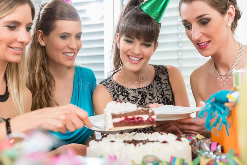 Cztery pięknego najlepszego przyjaciela i podczas gdy dzielący urodzinowego tort obrazy stock