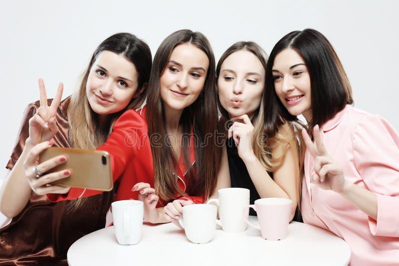 Cztery pięknej dziewczyny w piżamach siedzą przy stołem, piją i gawędzą w ogólnospołecznej sieci, herbaty lub kawy obraz royalty free