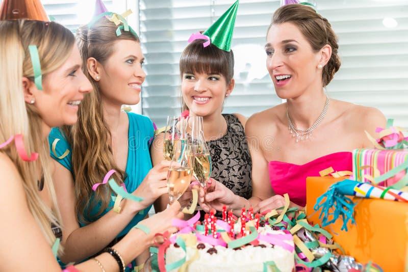 Cztery piękny i rozochocone kobiety wznosi toast z szampanem obrazy stock