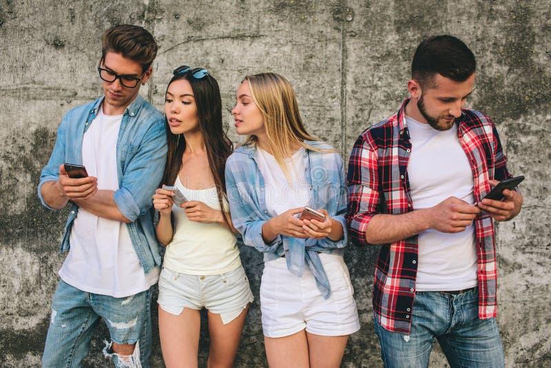 Cztery potomstwa i ruchliwie ludzie są trwanie na popielatym tle i patrzeć ich telefony wpólnie Są poważnym amd obraz royalty free
