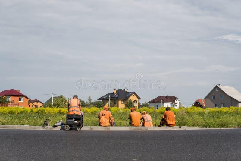 Cztery pracownika odpoczywa na budowy drogi miejscu z domy za one zdjęcie stock