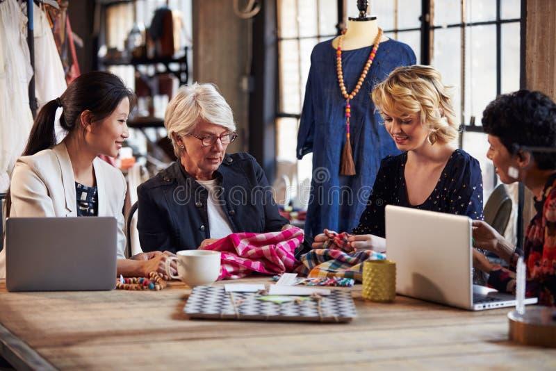 Cztery projektanta mody W spotkaniu Dyskutuje tkaniny obrazy royalty free