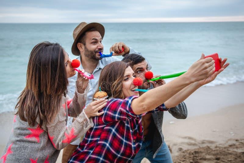 Cztery przyjaciela z czerwonymi nosami biorą selfie i świętują urodziny na plaży zdjęcia stock