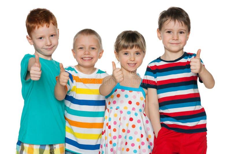 Cztery rozochoconego dziecka trzymają jego aprobaty obraz royalty free