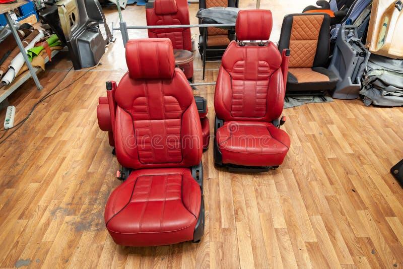Cztery sporta siedzenia z czerwonym rzemiennym podstrzyżeniem, lokalizować na podłodze w warsztacie dla naprawy i nastrajania sam obrazy stock