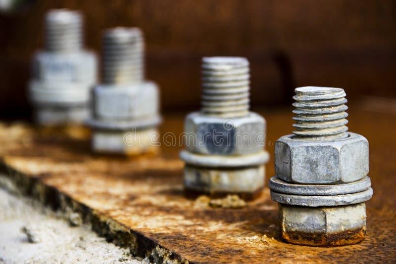 Cztery srebnej śruby na ośniedziałym metalu talerzu obrazy stock