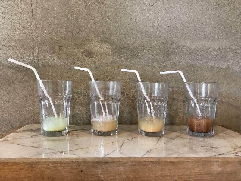 Cztery szkła z białymi słoma różna skończona lukrowa kawa na marmuru i drewna stole z cement ścianą typ zdjęcia stock