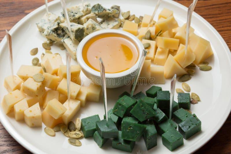 Cztery typu ser dobierający na białym talerzu, diced, obok miodu w pucharze, w górę zdjęcie royalty free