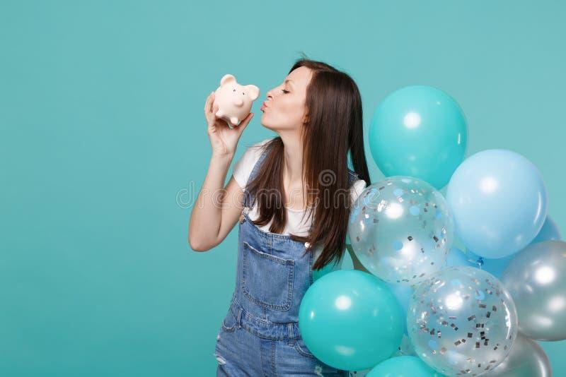 Czułej młodej kobiety dosłania powietrza podmuchowy buziak prosiątko pieniądze bank w ręce, odświętność, trzyma kolorowych lotnic obraz royalty free