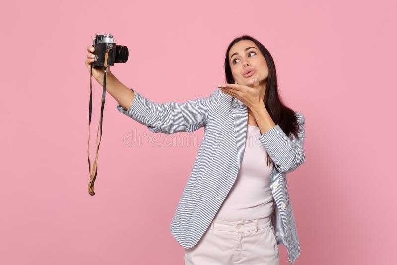 Czuła ładna młoda kobieta robi selfie strzelającemu na retro rocznik fotografii kamerze, podmuchowy dosłania powietrza buziak odi fotografia royalty free