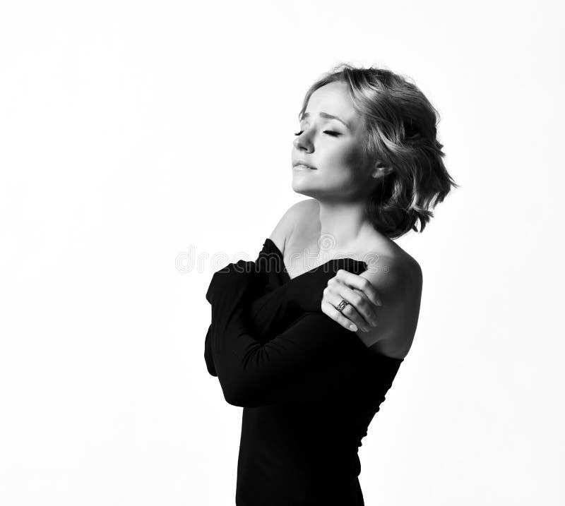 CzuÅ'a aktorka z krÄ™conymi wÅ'osami w barkowej czarnej sukience oblaÅ'a ramiona i zamknęła oczy zdjęcie royalty free