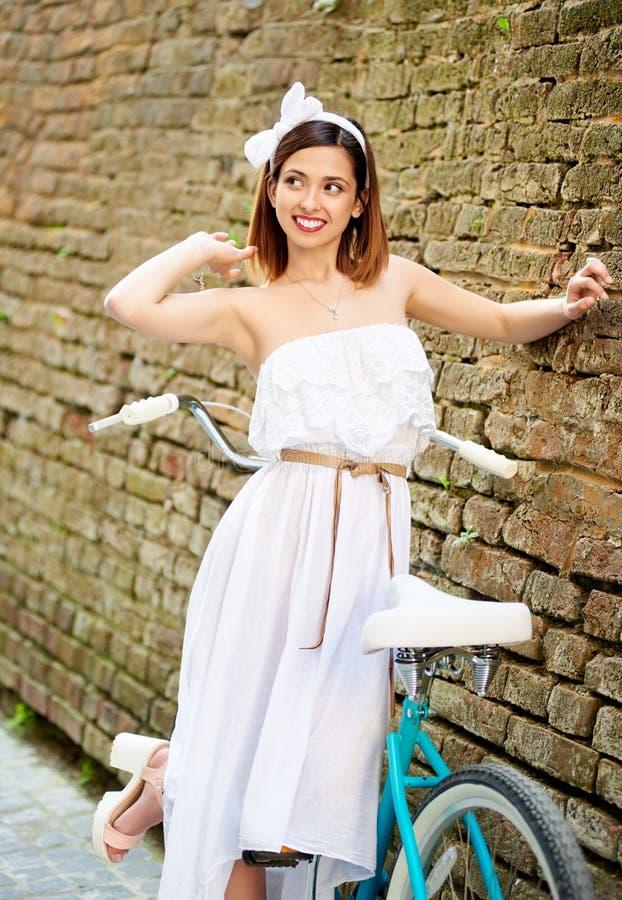 Czuła kobieta patrzeje figlarnie na boku blisko rocznika bicyklu, ściana z cegieł obrazy stock