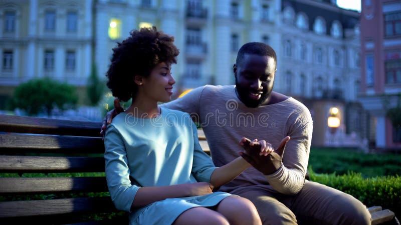 Czuła męska mienie dziewczyny ręka na ławce, romantyczna data w mrocznym mieście obraz royalty free