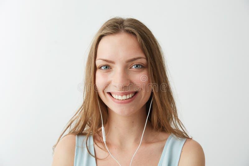 Czuła młoda ładna dziewczyna patrzeje kamery uśmiechniętego słuchanie lać się muzykę w hełmofonach nad białym tłem fotografia royalty free