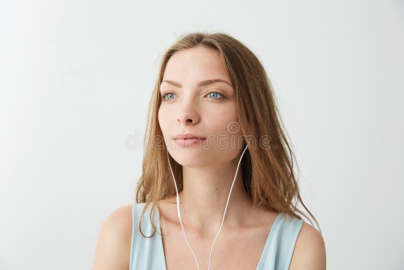 Czuła marzycielska młoda ładna dziewczyna marzy słuchać lać się muzykę w hełmofonach nad białym tłem obraz royalty free
