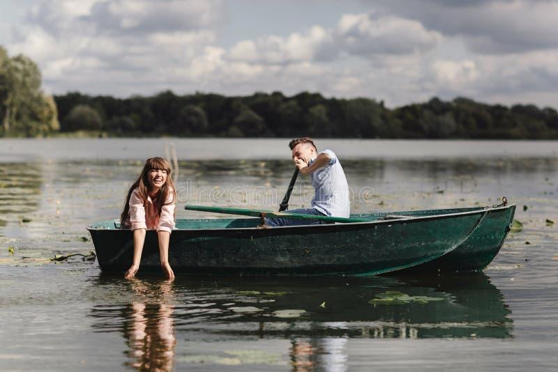 Czuciowy figlarnie Piękni potomstwa dobierają się cieszyć się romantyczną datę podczas gdy wiosłujący łódź Szczęśliwy mieć each i obraz stock