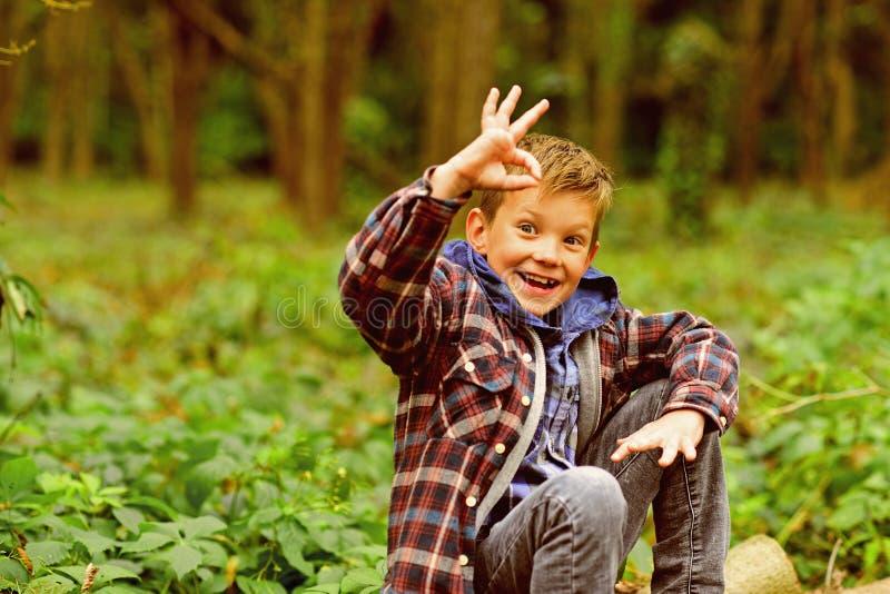 Czuję ok Chłopiec przedstawienia ok znak szczęśliwy mały chłopiec Mała chłopiec cieszy się dzień w drewnach Właśnie relaksuje, ev zdjęcia stock
