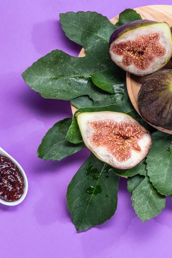 Czupirzy dżem z figami, figa liśćmi i białą łyżką z dżemem na purpurowym tle, obrazy royalty free