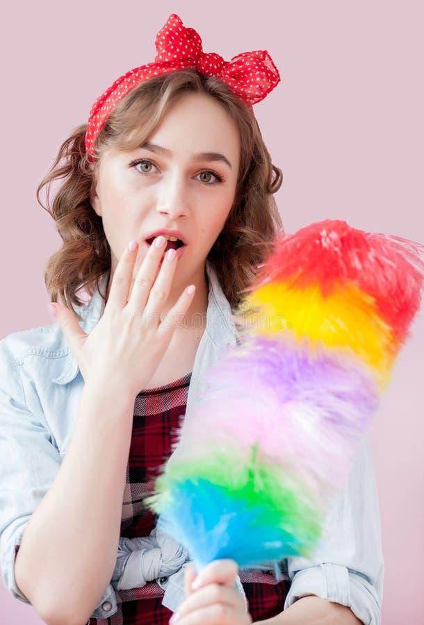 Czyścić wałkowy w górę kobiety Uśmiechnięta pinup dziewczyna trzyma kolorowego duster muśnięcie czyści usługa W górę dziewczyny c zdjęcia stock