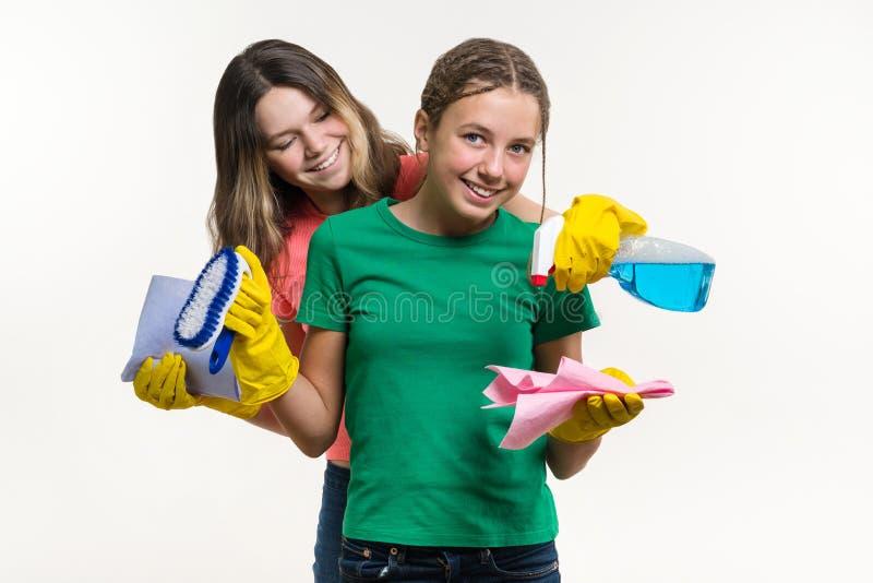 Czyścić, domowi obowiązki i pracy zespołowej pojęcie, Dwa nastoletniej siostry jest ubranym żółte ochronne rękawiczki i trzyma on zdjęcie royalty free