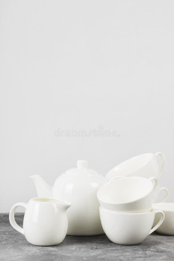 Czyści białego tableware teapot, filiżanki, spodeczki na szarym backgrou zdjęcia royalty free
