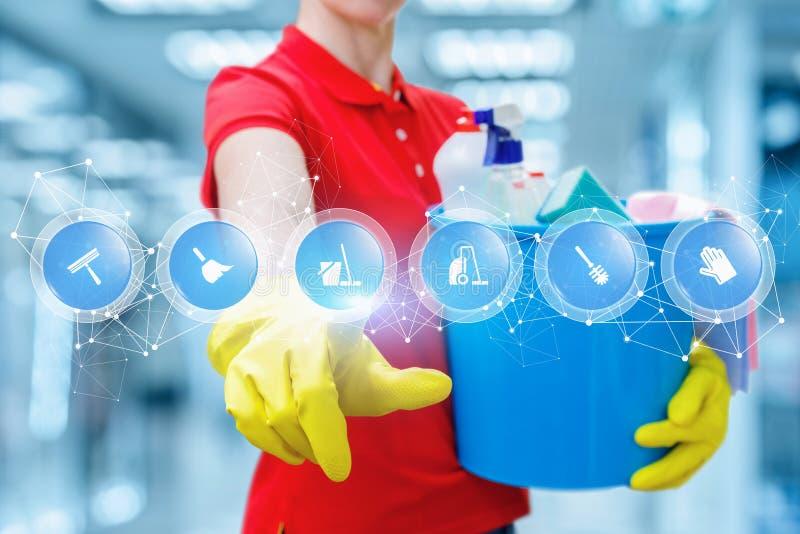 Czyści kobieta w gumowych rękawiczkach utrzymuje wiadro peł z substancjami chemicznymi i macaniem ekran z cyfrowym planem dużo obraz royalty free