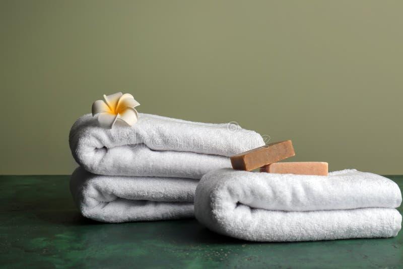 Czyści miękcy ręczniki z mydlanymi barami na koloru stole fotografia stock