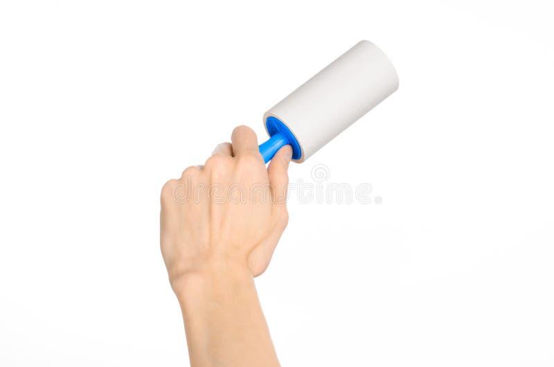Czyści odzieżowego domowego temat i czyścić: ludzka ręka trzyma błękitnego kleistego muśnięcie odzieżowy i meblarski dla czyścić  zdjęcia royalty free