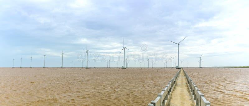 Czysta energia, siły wiatru roślina z drogą przemian gigantyczni silniki wiatrowi przy morzem zdjęcie stock