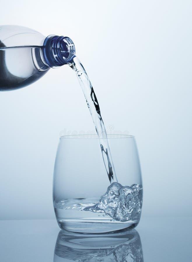 Czysta woda pitna płynie od butelki w jasnego szkło z pięknymi bąblami zdjęcia stock